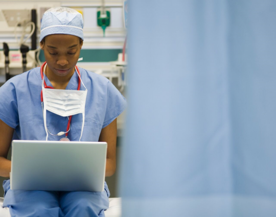 A medical professional uses a laptop.