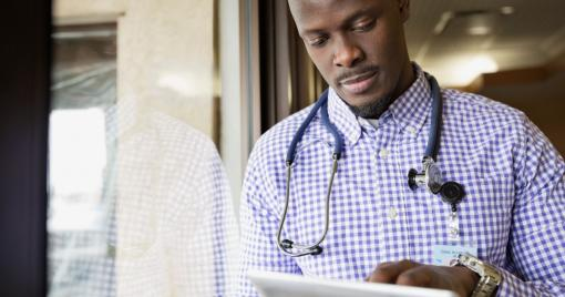 A man with a stethoscope looks at and touches a digital tablet.